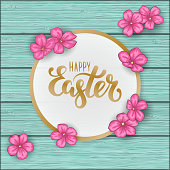 Happy Easter greeting card with flowers pink daisy on blue wooden table. Hand drawn brush pen lettering. design holiday greeting card and invitation of happy Easter day spring
