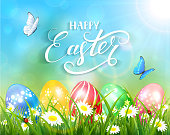 Happy Easter on blue background and eggs on grass