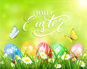 Happy Easter on green background and eggs on grass