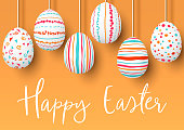 Happy Easter. pending easter eggs on golden background. Easter colorful hanging eggs with simple pink, orange, red, blue stripes