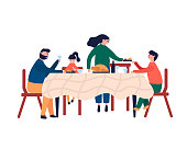 Happy family sitting at dinner table and eating turkey