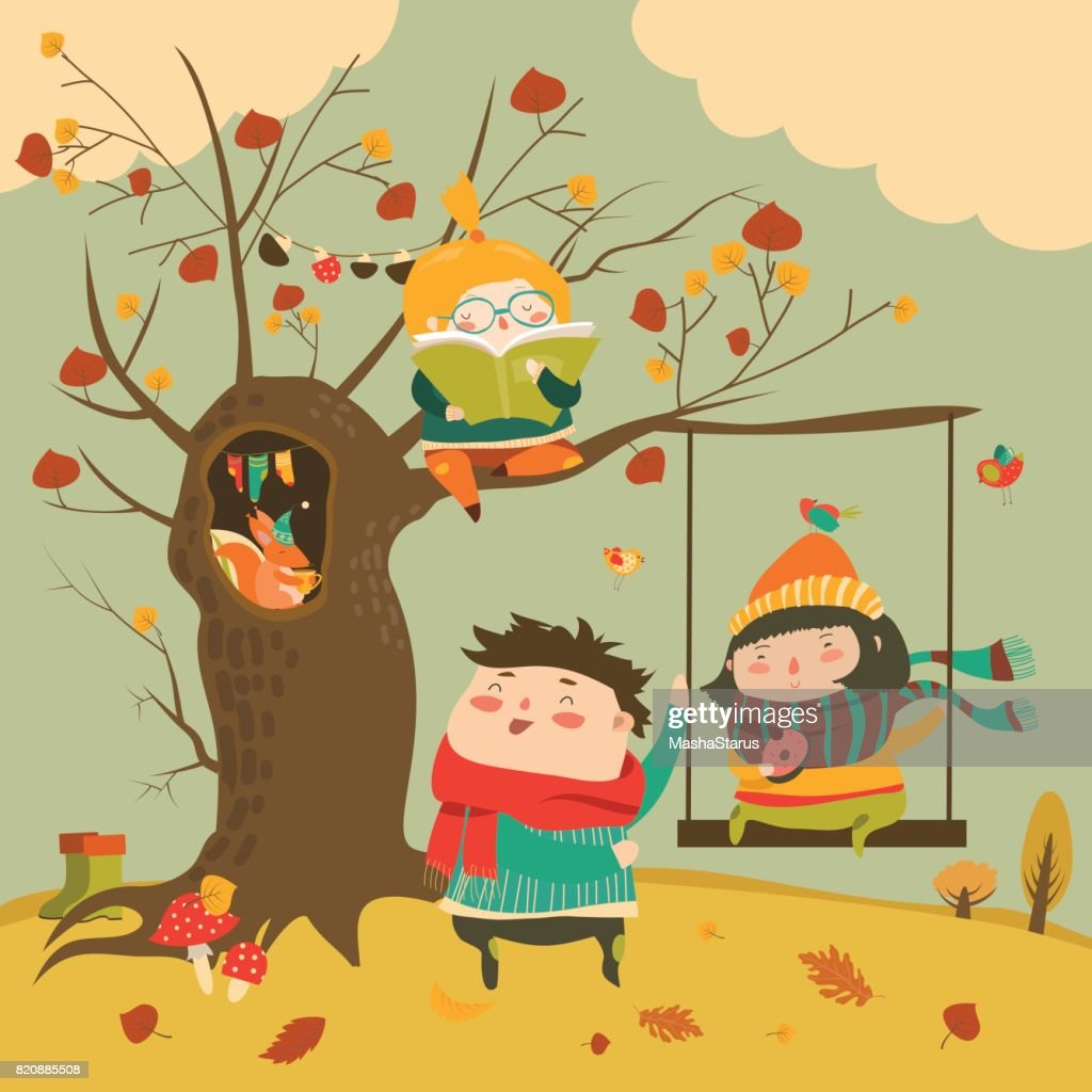 Happy kids ride on a swing in the autumn forest