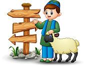 Happy muslim kid holding sheep with blank wood arrow sign