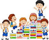 Happy schoolkids playing with stack of books
