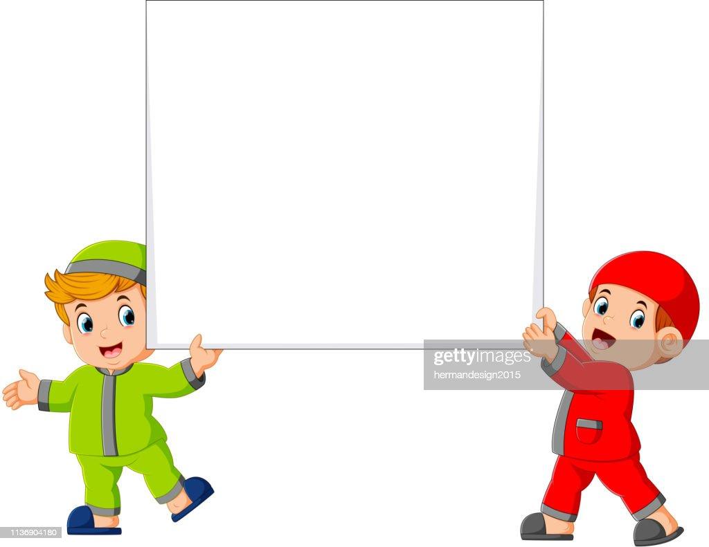 Happy two moslem boy holding big blank sign