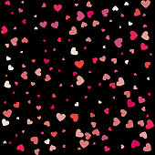 Heart confetti of Valentines petals falling on black background. Flower petal in shape of heart confetti for Women's Day