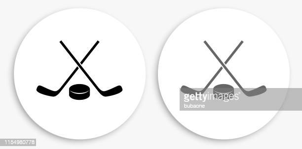 hockey stick and puck black and white round icon - hockey stick stock illustrations
