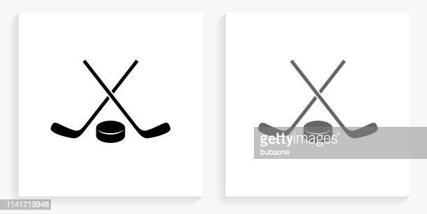 hockey stick and puck black and white square icon - hockey stick stock illustrations