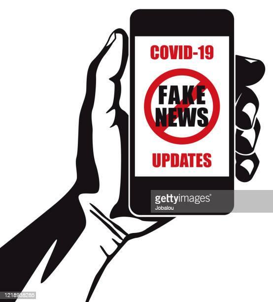 ilustrações, clipart, desenhos animados e ícones de segurando portátil anunciando coronavírus fake news - fake news