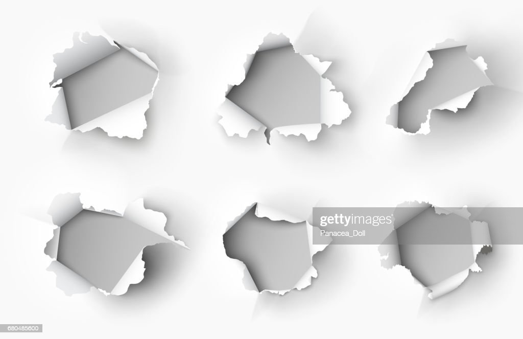 Holes torn in paper on white background
