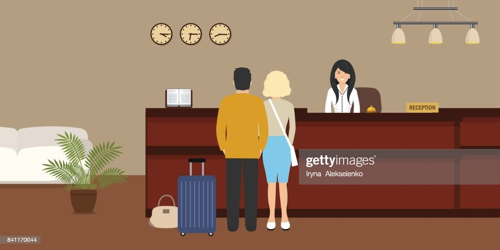 Hotel reception. Young woman receptionist stands at reception desk. There are also visitors here