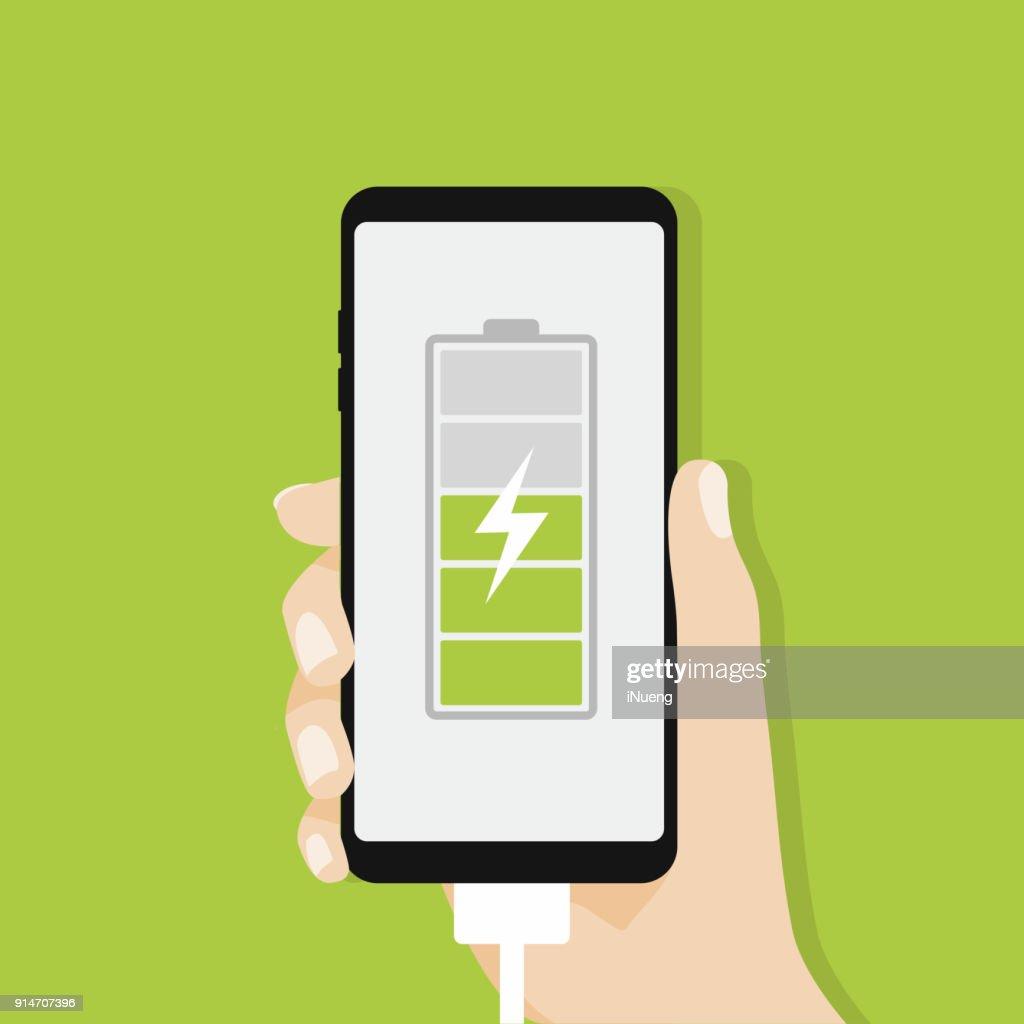 Human hand holding smartphone charging.