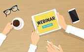 Human hands hold a tablet pc with webinar invitation on