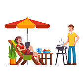 Husband doing barbecue, wife lying on lounger