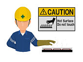 Industrial worker is presenting hot surface sign