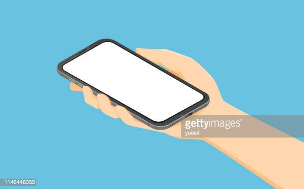 isometric hand holding smartphone - telephone stock illustrations