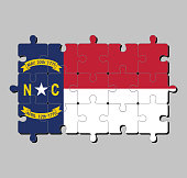 Jigsaw puzzle of North Carolina flag in blue union, a white star with N and C, the circle containing the same to be one-third.