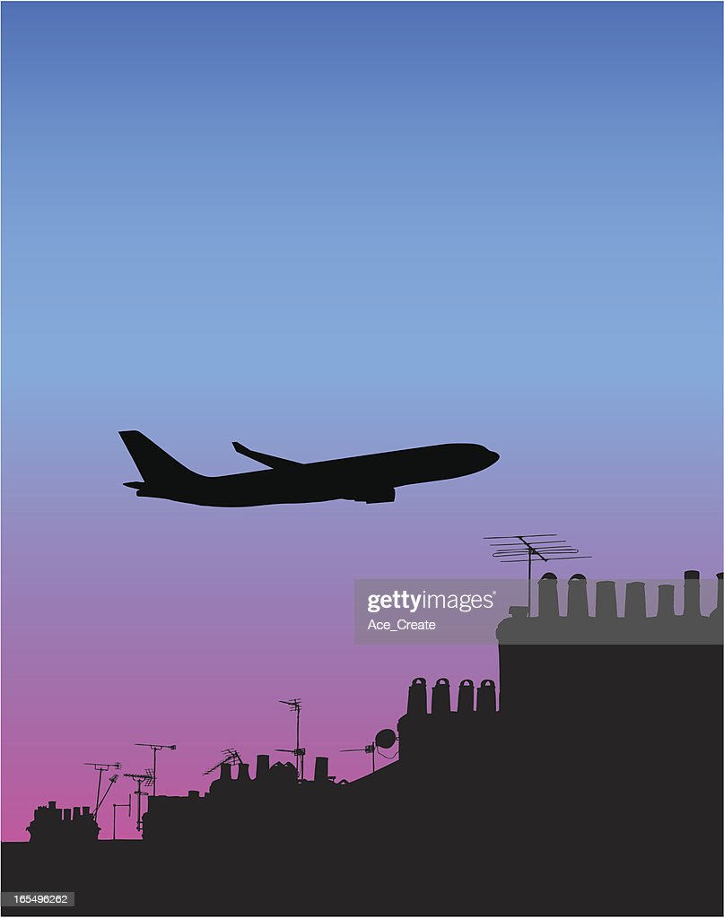 jumbo jet silhouetted above old roofscape