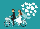 Just married couple bride and groom riding tandem bicycle