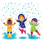 Kids in raincoats and rubber boots playing