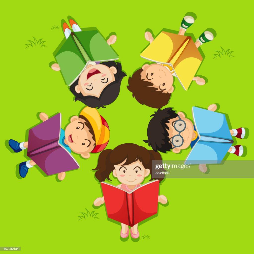 Enfants Lecture De Livre Sur Lherbe Verte Illustration - Getty Images