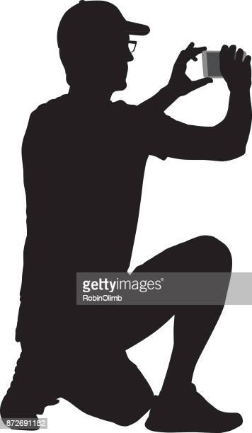 Kneeling Man Taking Picture With Smart Phone