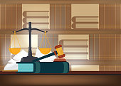 Law books with a judge's gavel on a table and book shelves on background.