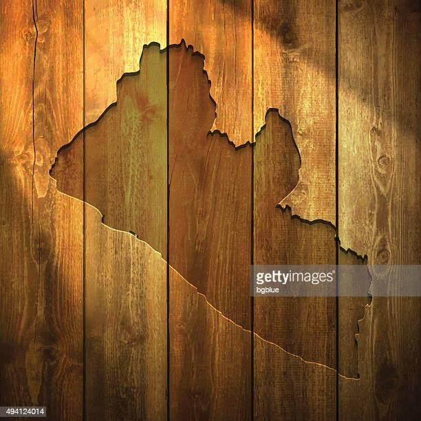 liberia map on lit wooden background - liberia stock illustrations, clip art, cartoons, & icons