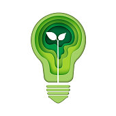 Light bulb icon with green abstract paper art