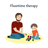 Little boy and a his father sitting on a floor and playing with blocks. Floortime therapy technique, used for teaching kids, especially for children with ASD or autism