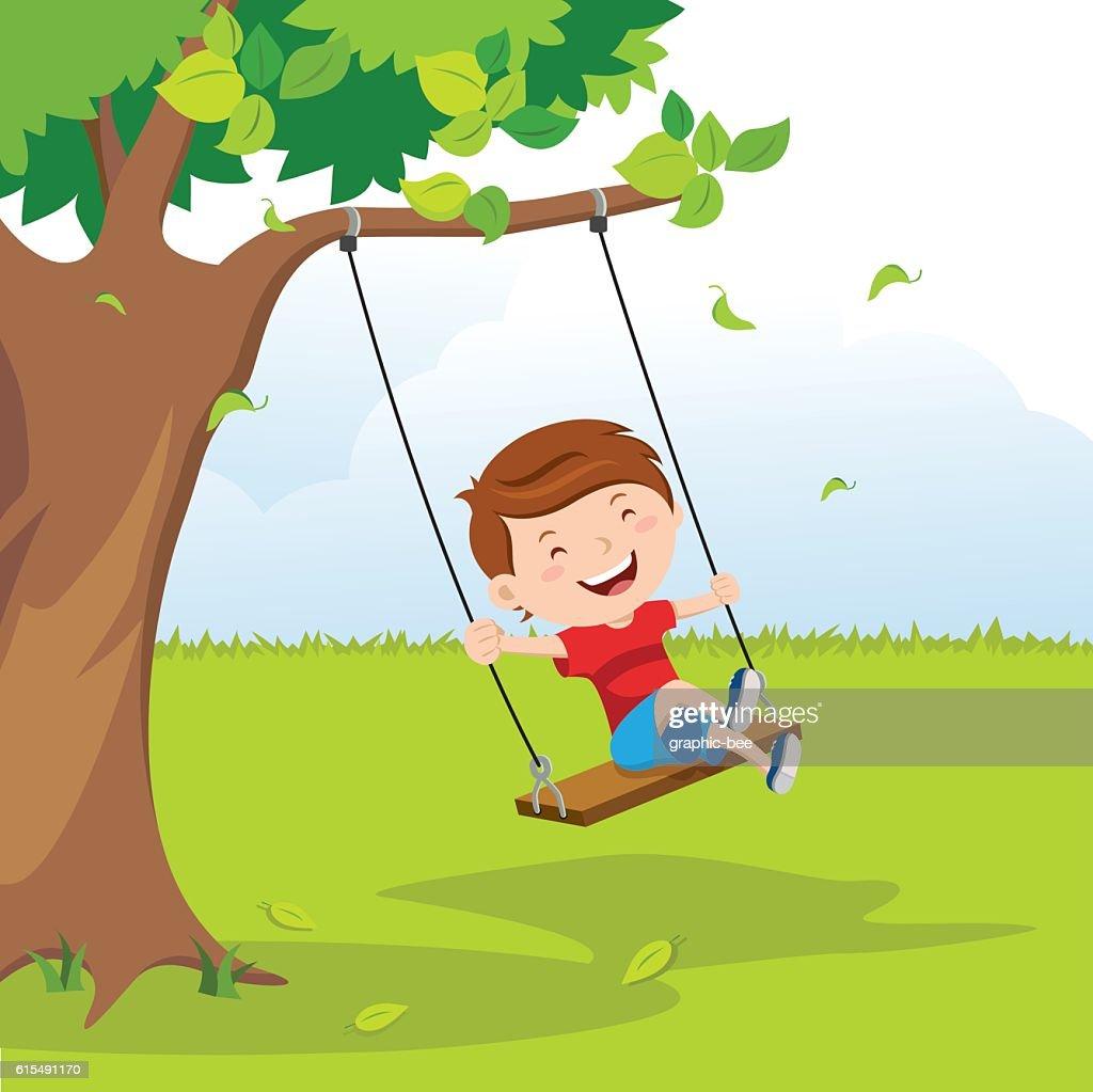 Little boy on swing under a tree