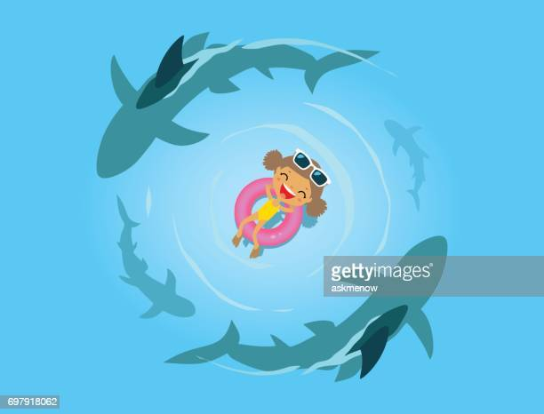 Little girl and sharks in the sea