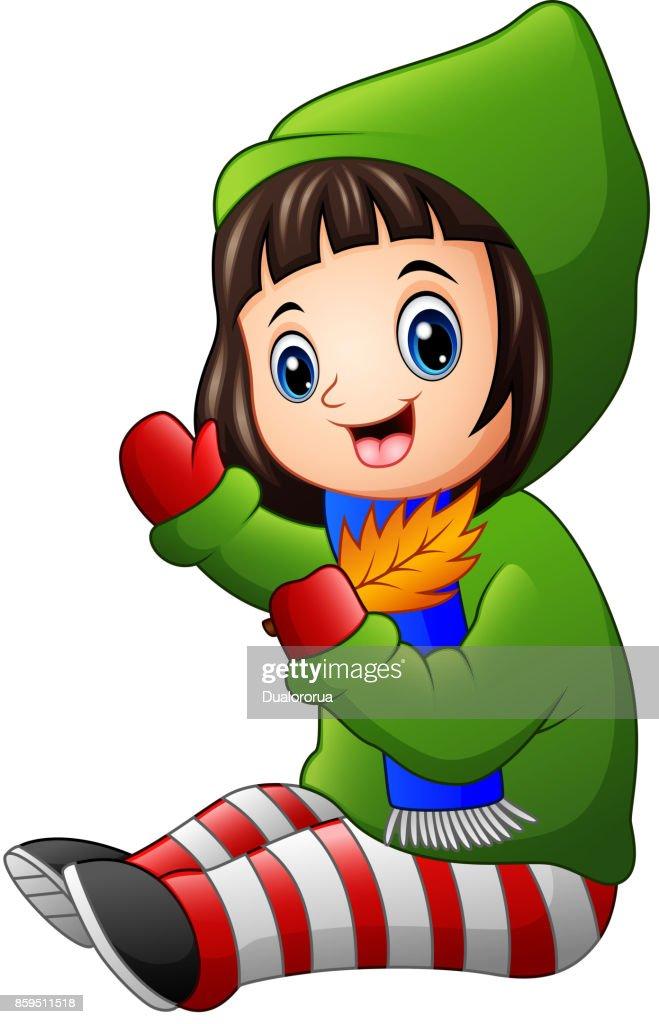 Little girl in green winter jacket holding autumn leaves