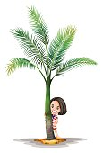 Little girl standing behind palm tree