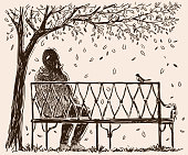A lonely girl sits o a bench in an autumn park