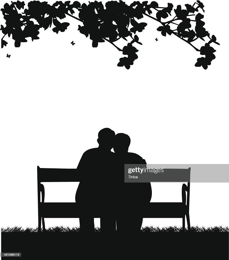 Lovely retired elderly couple sitting on bench in garden