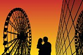 Lovers in amusement park at sunset