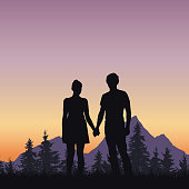 Loving young man and woman on grass at tree and mountains under romantic sky with dawn - vector