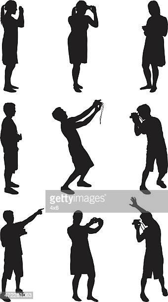 male and female silhouettes taking pictures with camera - camera stand stock illustrations, clip art, cartoons, & icons