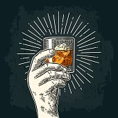 Male hand holding glass whiskey with ray. Vintage vector engraving