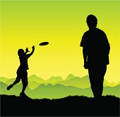 Man and boy play frisbee