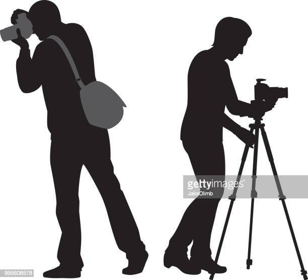 man and woman with cameras and tripod silhouette - camera stand stock illustrations, clip art, cartoons, & icons