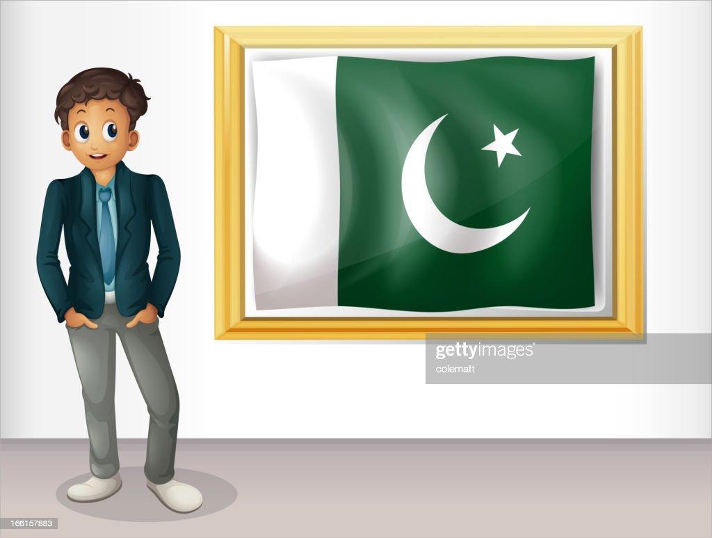 Man beside the framed flag of Pakistan