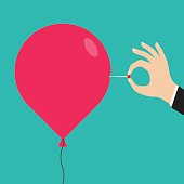 Man hand with a needle pierces the balloon