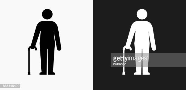 man holding a cane icon on black and white vector backgrounds - walking cane stock illustrations