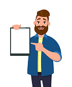 Man holding/showing a blank clipboard and pointing with index finger to it. Vector illustration in cartoon style.