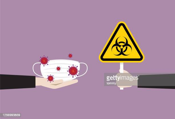 a man holds a biohazard symbol to a used mask - biohazardous substance stock illustrations