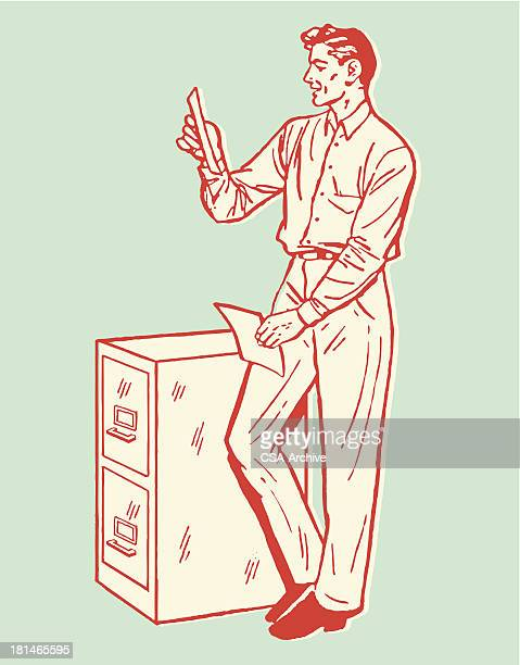 Man Looking at Files and Leaning on File Cabinet