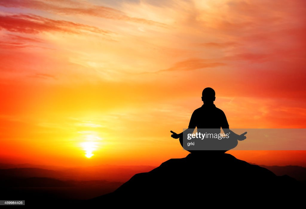 Man meditates on beautiful mountain dusk.
