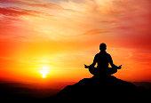 Man meditates on beautiful mountain dusk.